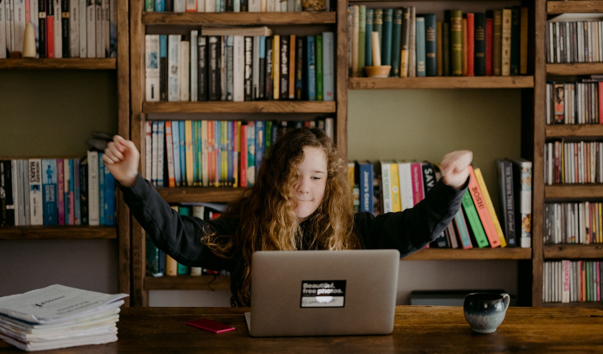 Teen completing assignment on laptop